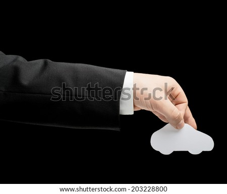 Caucasian male hand in a business suit, holding the white paper car shape, low-key lighting composition, isolated over the black background - stock photo