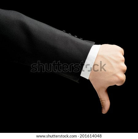 Caucasian male hand in a business suit, showing dislike thumbs down gesture sign, low-key lighting composition, isolated over the black background - stock photo