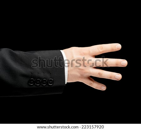 Caucasian male hand in a business suit showing number four with fingers, low-key lighting composition, isolated over the black background - stock photo