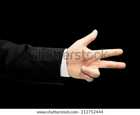 Caucasian male hand in a business suit showing number three with fingers, low-key lighting composition, isolated over the black background - stock photo
