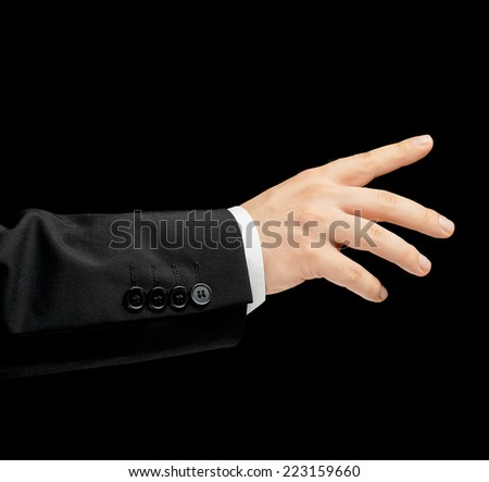 Caucasian male hand in a business suit, showing pointing gesture sign, low-key lighting composition, isolated over the black background - stock photo