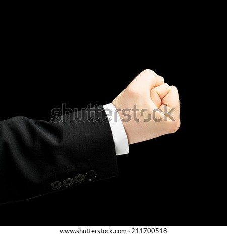 Caucasian male hand in a business suit, showing the clenched in the fist gesture sign, low-key lighting composition, isolated over the black background - stock photo