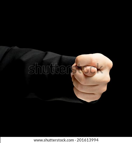Caucasian male hand in a business suit, showing the offensive fig gesture sign, low-key lighting composition, isolated over the black background - stock photo