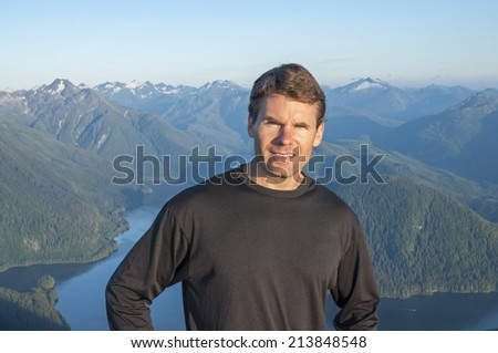 Caucasian male hiker in black shirt stands on top of mountain with beautiful scenic view of bay and mountains of Baranof Island in Alaska - stock photo
