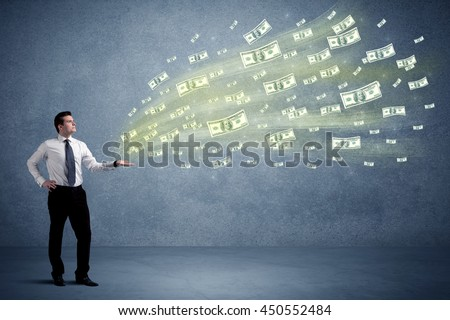 Caucasian male in business suit holding money,which flies through his hands - stock photo