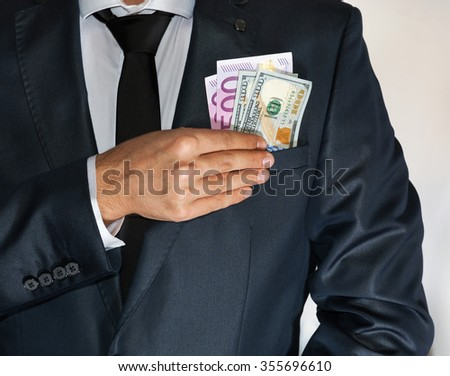 Caucasian male in suit holding lots of money in his pocket