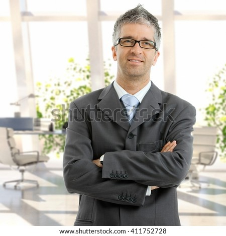 Caucasian male mid adult business expert standing arms crossed at office. Wearing suit and glasses. - stock photo