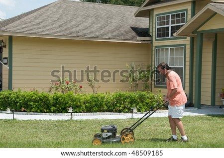 Caucasian male mowing the lawn in front of a single family residence. Close up.