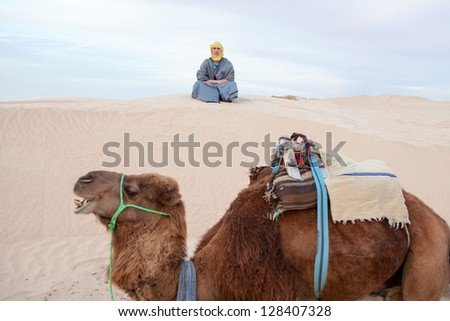 Caucasian male person sitting on sand dune in desert with camel on foreground - stock photo