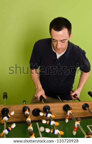 Caucasian male playing Foosball, table football / soccer - stock photo