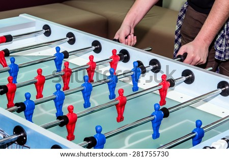 caucasian male playing table soccer football game - stock photo