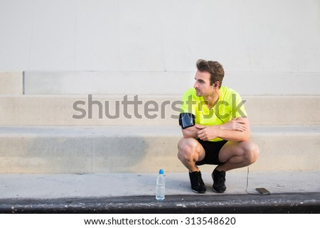 Caucasian male runner looking to the copy space area for your text while having a rest after workout training, male runner listen to music in headphones though cell phone and admiring city landscape - stock photo