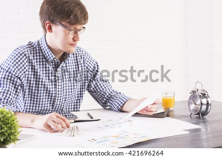 Caucasian male sitting at office desk with alarm clock and business sketch and looking at paper sheet