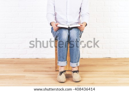 Caucasian male sitting in empty brick interior with wooden floor, reading book placed on his lap - stock photo