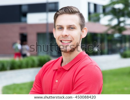 Caucasian male student with stubble looking at camera - stock photo