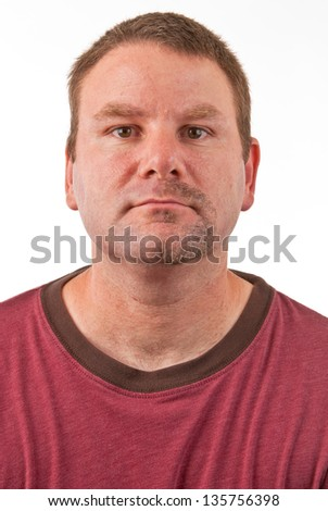 Caucasian male with a half shaved goatee facing forward. The right side of the man's goatee has been shaved, as though he is in the process of shaving. - stock photo