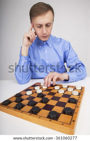 Caucasian man at a table playing checkers on a white background
