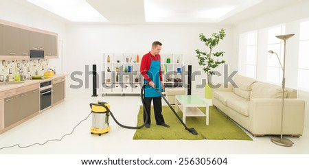 caucasian man cleaning carpet with vacuum cleaner in living room - stock photo