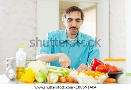 Caucasian man cooking  vegetables at home kitchen - stock photo