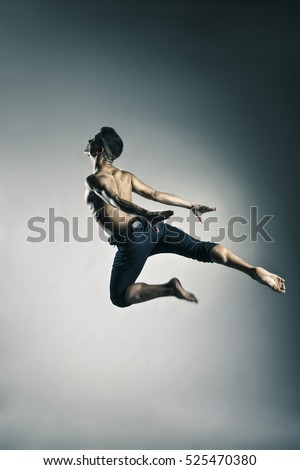 Caucasian man gymnastic leap posture on grey