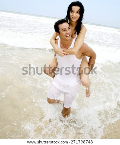 Caucasian man having his woman piggyback on his back - stock photo