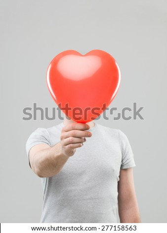 caucasian man holding heart shaped ballon in front of his head, against grey background