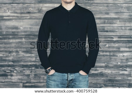 Caucasian man in black shirt and jeans standing in front of wooden wall. Mock up - stock photo