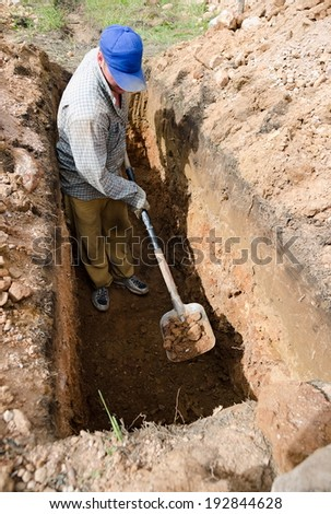 Caucasian man in blue cap digs grave at cemetery