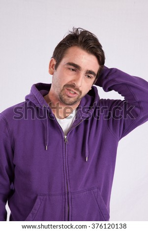 Caucasian man in purple sweatshirt with a hood, looking thoughtful  - stock photo