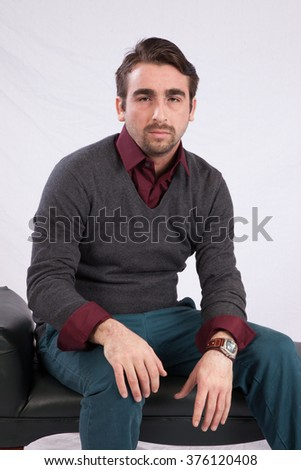 Caucasian man in sweater sitting and  looking thoughtful   - stock photo