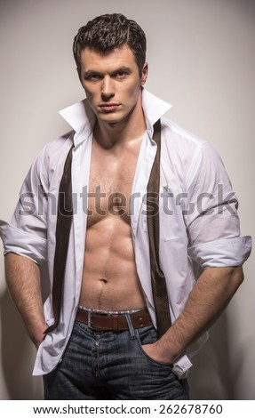 Caucasian man is wearing an unbuttoned shirt with neck tie around neck. - stock photo
