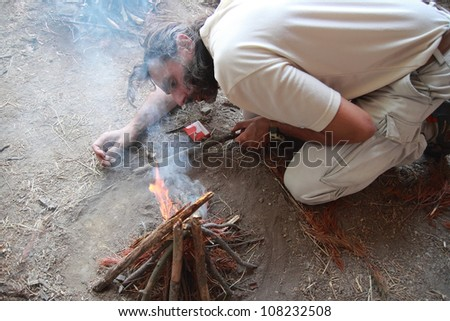 caucasian man lighting a fire camp - stock photo