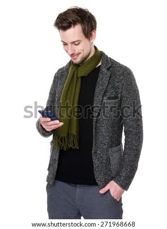 Caucasian man looks at cellphone - stock photo