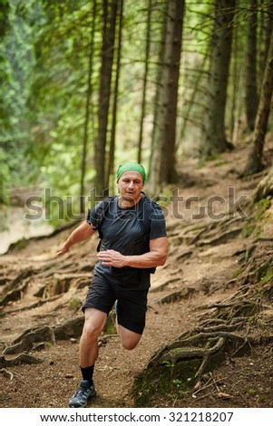 Caucasian man running in the pine forest forest, outdoor fitness concept