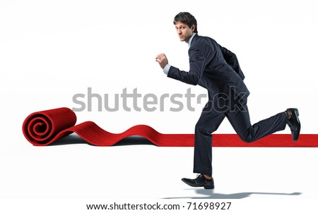 caucasian man running with  rolling red carpet