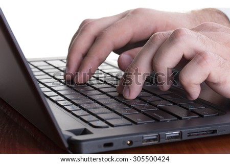 Caucasian man's fingers pressing buttons of a gray laptop
