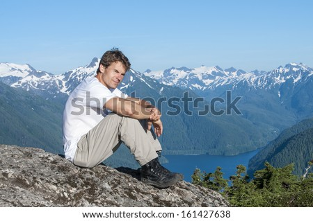 Caucasian man sits on rock on mountain peak overlooking beautiful southeast Alaska landscape including Silver Bay and mountains of Baranof Island on clear summer day - stock photo
