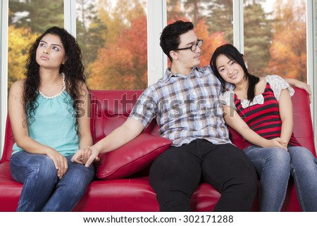 Caucasian man sitting on the sofa with his girlfriend while holding hands with his affair - stock photo