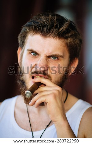 caucasian man smoking a cigar, looking at camera. maybe a gangster, gambler or a mafioso character he is enveloped in a cloud of cigar smoke. He is wearing a t-shirt and he has beard  - stock photo