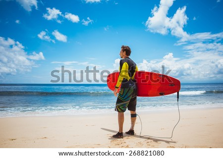 Caucasian man stay on the beach with his red longboard surf and look to the sea, blue sea and sky on background - stock photo