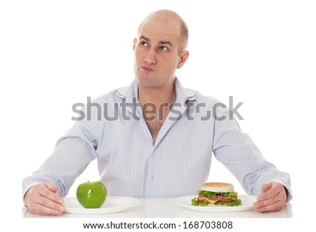 Caucasian man undecided if he is gonna go for the apple or for the hamburger, isolated on white background.