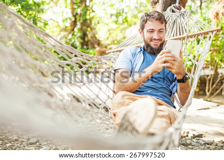 caucasian man using mobile phone white swinging in a hammock