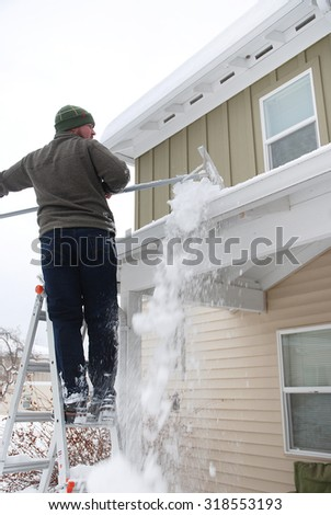 Caucasian man using rake to shovel heavy snow off roof