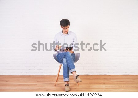 Caucasian man with coffee and tablet in hands sitting on chair in interior with brick wall and wooden floor - stock photo