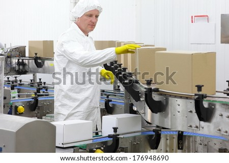 caucasian man worker in white apron, cap and yellow gloves at production line in factory