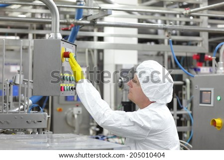 caucasian man worker in white apron, cap and yellow gloves at production line in factory,pressing buttons at control panel  - stock photo