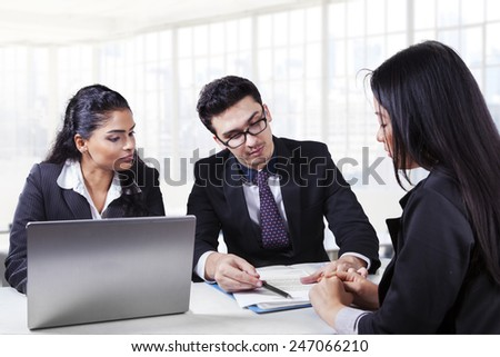 Caucasian manager with his assistant showing and explaining a paperwork to their client - stock photo