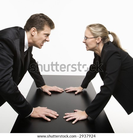 Caucasian mid-adult businessman and woman staring at each other with hostile expressions. - stock photo