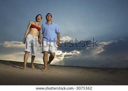 Caucasian mid-adult couple holding hands walking on beach.