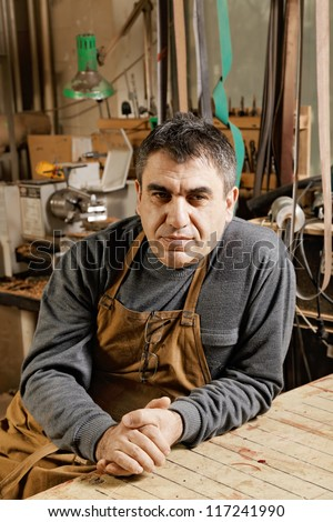 Caucasian middle-aged artisan sitting in his workshop at workbench and looking sideways - stock photo